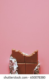 top view of chocolate bar on pink background with copy space