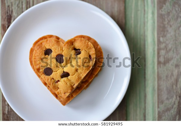 Top view of chocolate chip cookies in the shape of heart on white plate, with wooden background. (Concept about love and relationship)