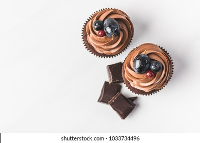 top view of chocolate cupcakes with cream, grape, berries and pieces of chocolate isolated on white