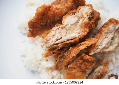 Top view of chopped deep fried chicken on top of rice.