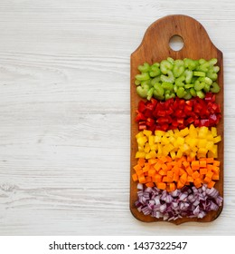 Top view, chopped fresh vegetables (carrot, celery, red onion, colored peppers) arranged on cutting board on a white wooden surface. Flat lay, from above, top view. Copy space.