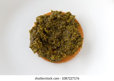 Top view of chopped parsley spread on a snack cracker atop a white plate.