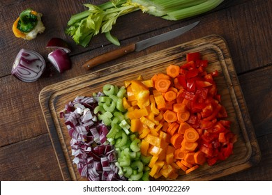 Top view chopped vegetables arranged on cutting board on wooden table