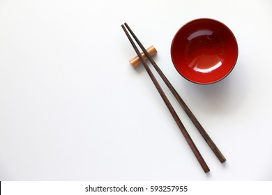 Top view of chopsticks red bowl on white table background.Flat lay