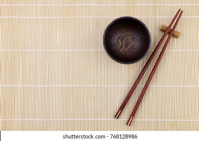 Top view chopsticks and Wood bowl on bamboo table background.Flat lay