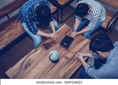 top view of Christian group are praying around wooden table with  blurred  world globe, holy bible and small wooden cross, christian background , pray for the world concept