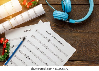Top view Christmas background.music note paper with decoration and headphones on wooden table with copy space.