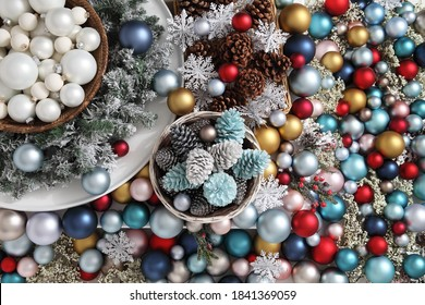 top view christmas decorations centerpiece with garland and balls near a basket with pine cones, isolated on a heap of colorful and shiny balls