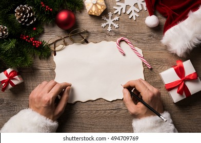Top view of christmas letter in santa claus hand. Close up of hands holding empty wishlist on wooden table with xmas decoration. High angle view of santa claus hands writing on a paper with gifts.