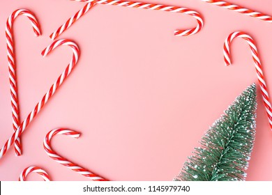 Top view of Christmas tree with many candy cane on pastel pink  background.Holiday festive celebration greeting card with copy space to addng text