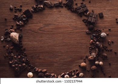 top view of circle made of various types of chocolate pieces, truffles, coffee grains and cocoa beans on wooden table