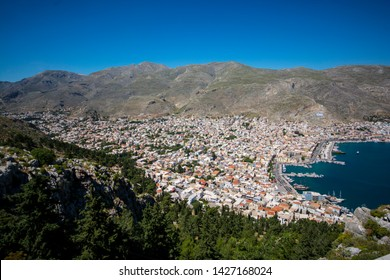 top view of the city Kalymnos with beautiful white and colorful houses between mountains, forest and sea In greece Island Kalymnos