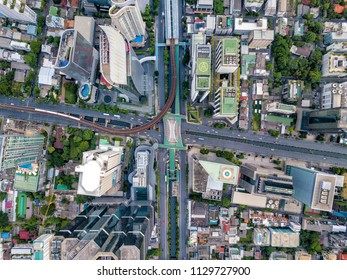 Top view of city road junctions in heart of business center on sathorn and silom district at Bangkok city Thailand. Aerial view of BTS Skytrain run into the smart city at Bangkok downtown in Thailand.