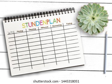 top view of class schedule or timetable template with word STUNDENPLAN, German for schedule, on notepad against rustic white wooden table