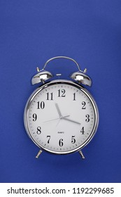 Top view of a classic alarm clock on dark blue background with copy space