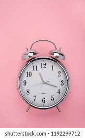 Top view of a classic analog alarm clock on pink background with copy space