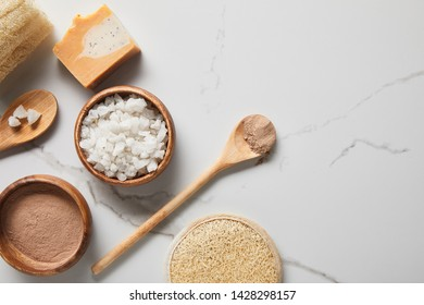 top view of clay powder and sea salt in wooden bowls on marble table near spoons, soap and loofah
