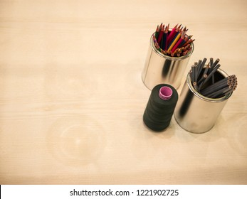 Top view of clean desk with tin cans of dark and colorful pencils and a dark thread reel