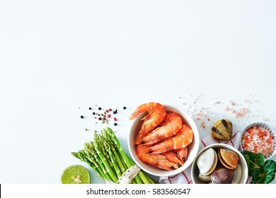 Top view of clean eating ingredients over white background with a copy space. Cooked prawns, clamps, asparagus, lime, salt and pepper.