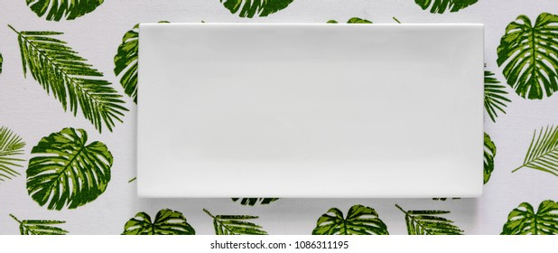 Top view of clean white plate on Palm leaves tablecloth, top view