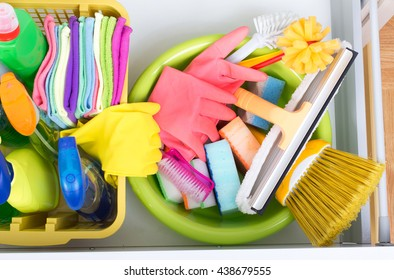 Top view of cleaning supplies and equipment stored in drawer in kitchen cabinet