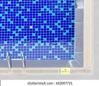 Top view of clear blue swimming pool with steel ladder and number depth indicate on poolside.