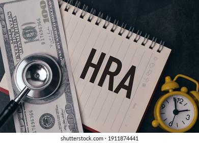 Top view of clock, money banknote, stethoscope and notebook written with text HRA stands for Health Reimbursement Arrangement. - Shutterstock ID 1911874441