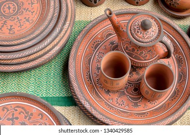 Top view close up of beautiful Gujarati Khavda Pottery earthen terracotta crockery tea cups, kettle and tray at a roadside market exhibition stall at Dilli Haat, New Delhi, India