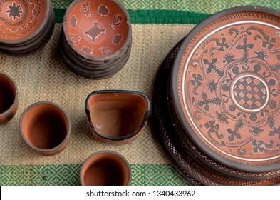 Top view close up of beautiful Gujarati Khavda Pottery earthen terracotta plates, bowls, glasses / mugs at a roadside market exhibition stall at Dilli Haat, Delhi, India