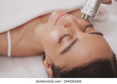Top view close up of a beautiful happy woman getting microcurrent facial treatment at beauty clinic. Attractive female patient enjoying skincare procedures by professional cosmetologist