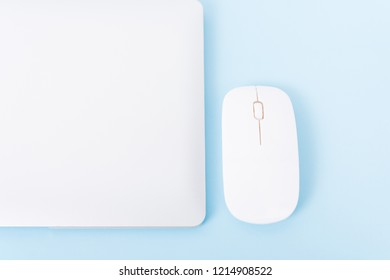 Top view close cover laptop computer notebook and wireless mouse isolated on blue background