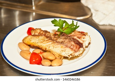 Top view, close distance of a freshly prepared filet of red snapper fish with a base of white bean and pepper salad and halved cherry tomatoes, on a round, white disth with a blue rim