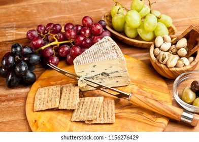 Top  view, close distance of spanish tapas of a wedge of blue cheese, cheese knife on a round, rare wood plate, bowls of olives, pistachio nuts with a variety of freshly picked grapes and crackers