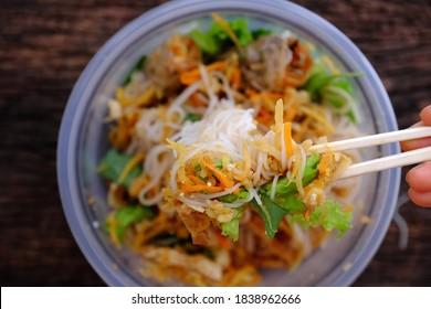 Vue de dessus en gros plan des baguettes tenant la main ramassent de la nourriture à servir sur commande en ligne dans un bol en plastique, des rouleaux de printemps frits avec des nouilles de riz végétalien