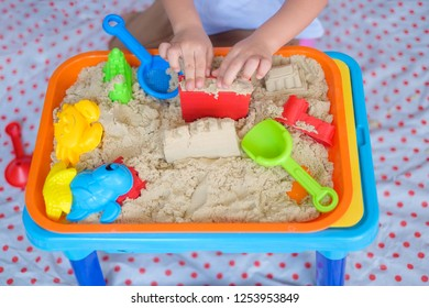 Top view close up of little Asian 2 - 3 years old toddler boy playing with kinetic sand at home ,Fine motor skills development, Montessori education, Creative play for kids concept