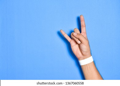 Top view close up of Men hand of posting rock with empty white wristband on colorful pastel on background view. Flat lay creative wallpaper.