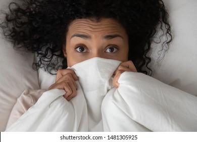 Top view close up of millennial african American girl lying in bed covered with white sheets look at camera, black young woman peer out of warm fluffy duvet, relaxing waking up in bedroom