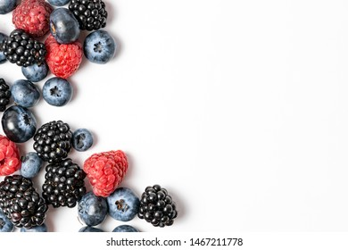 Top view and close up of mix ripe, yummy and sweet blueberries, blackberries, raspberries fruits on white background with copy space