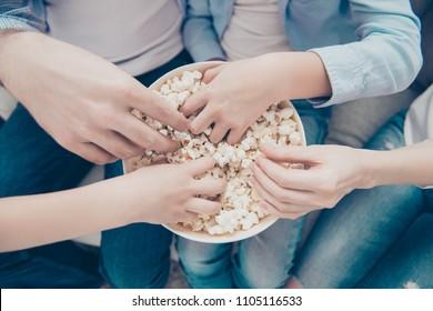 Top view close up portrait of hands taking sweet pop corn from bucket, dad mom kids sharing popcorn while watching film program tv, sitting on sofa indoor, enjoying free time having fun