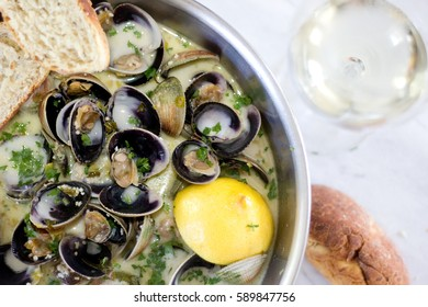 Top view and Close up of steamed clams with white wine, butter and garlic in a bowl. Garnished with lemon, parsley and bread slices. Served with a glass of white wine.