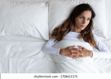 Top view close up thoughtful woman lying on one half of empty bed alone, insomnia, lack of sleep, upset girl thinking about personal problems, bad relationship, break up with boyfriend or divorce