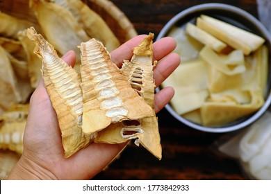 Vue de dessus en gros plan femme tenant des pelles de bambou séchées sur fond bambou, matière première pour de nombreux aliments vietnamiens