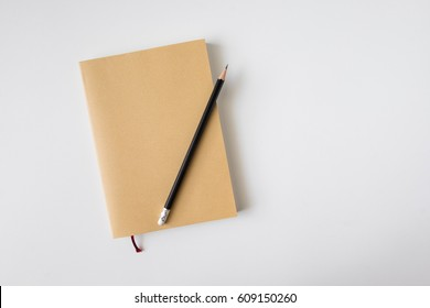 Top view of closed blank craft paper cover notebook with pencil on white desk background
