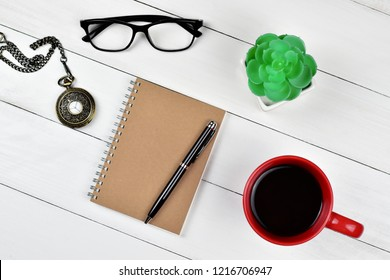 Top view of closed brown spiral notebook with black pen on top, a red coffee mug, green Kalanchoe in a pot, glasses and ancient locket clock on white wooden background, diary and blog writing concept