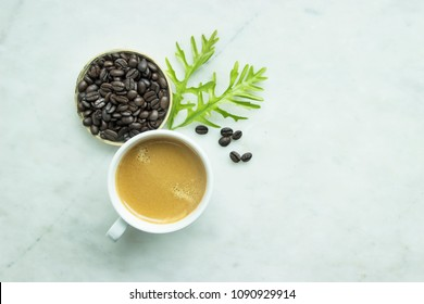 Top view, Closed up fresh mug coffee and green leave, beans in wooden tray on grey background, this menu made from dark roasted coffee. Recipe to make drink including Espresso, Americano, Mocha, Latte