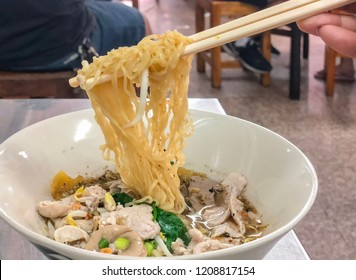 Top view and closed up of pork, pork offal noodle with spicy Thai style soup in white bowl and chopsticks in hand. Selective focus with blurred background