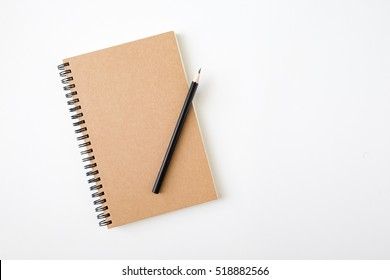 Top view of closed spiral blank craft paper cover notebook with pencil on white desk background