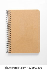 Top view of closed spiral blank recycled paper cover notebook on white desk background