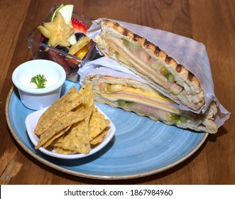 A top view closeup of a delicious cheese and ham sandwich, nachos and a tiny bowl of fruit on a plate