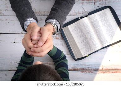 Top view closeup of a father and his little son's hands praying together after bible study in the morning. Christianity, Parenting and Raising child in God's way, Thankful moment, Happy father's day.